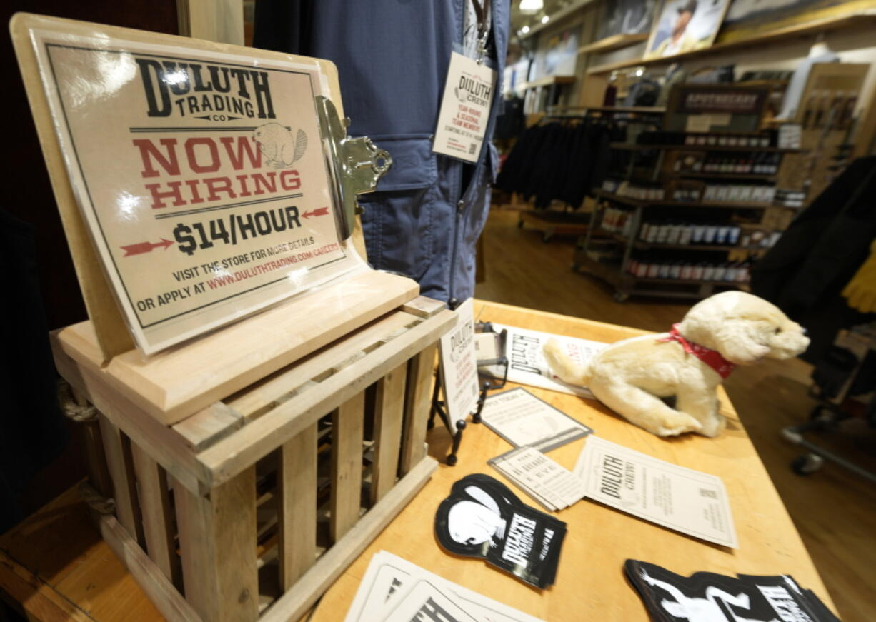 A now hiring sign sits on a display in a clothing store Saturday, Oct. 9, 2021, in Sioux Falls, S.D.  The number of Americans applying for unemployment benefits fell to its lowest level since the pandemic began, a sign the job market is still improving even as hiring has slowed in the past two months.