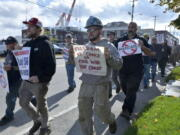 Justin Paetow, center, a tin shop worker at Bath Iron Works, takes part in a demonstration against COVID-19 vaccine mandate outside the shipyard on Friday, Oct. 22, 2021, in Bath, Maine.