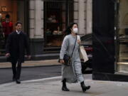 A woman wears a face mask as she walks in London, Tuesday, Oct. 19, 2021. Many scientists are pressing the British government to re-impose social restrictions and speed up booster vaccinations as coronavirus infection rates, already Europe's highest, rise once more. The U.K. recorded 49,156 new COVID-19 cases on Monday, Oct. 18, the largest number since mid-July.