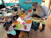 Amy McCoy serves lunch to preschoolers at her Forever Young Daycare facility, Monday, Oct. 25, 2021, in Mountlake Terrace, Wash. Child care centers once operated under the promise that it would always be there when parents have to work. Now, each teacher resignation, coronavirus exposure, and day care center closure reveals an industry on the brink, with wide-reaching implications for an entire economy's workforce.