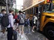 FILE -- In this Sept. 13, 2021, file photo, students board a school bus on New York's Upper West Side. Even as most students return to learning in the classroom this school year, disruptions to in-person learning, from missing one day because of a late school bus to an entire two weeks at home due to quarantine, remain inevitable as families and educators navigate the ongoing pandemic.
