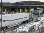 FILE - In this Wednesday, March 18, 2020 file photo, truck traffic from Canada waits to cross the border into the United States in Derby Line Vt. The U.S. will reopen its land borders to nonessential travel next month, ending a 19-month freeze due to the COVID-19 pandemic as the country moves to require all international visitors to be vaccinated against the coronavirus. The new rules, to be announced Wednesday, Oct. 13, 2021 will allow fully vaccinated foreign nationals to enter the U.S.