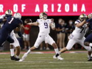 Washington quarterback Dylan Morris (9) throws a pass during the first half of the team's NCAA college football game against Arizona on Friday, Oct. 22, 2021, in Tucson, Ariz.
