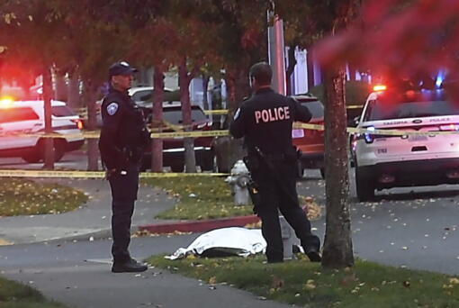 Tacoma police stand by a covered body at the scene of a shooting in Tacoma, Wash. Thursday, Oct. 21, 2021.